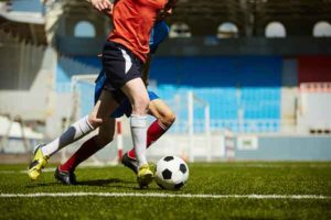 Two footballs playing on a professional pitch