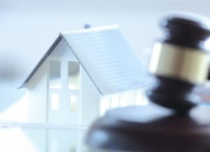 Close up White Miniature House on Top of the Table Beside Court Gavel