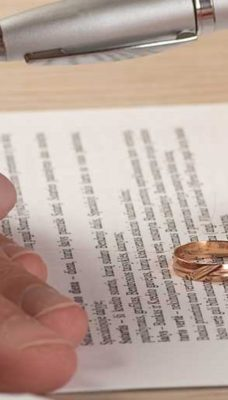 Woman giving her wedding ring back to her husband while signing a separation and divorce contract