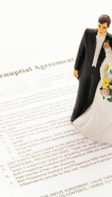 A figurine of a bride and groom on a prenuptial agreement